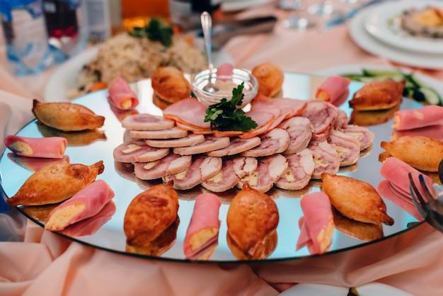 ベーコンと豚肉をチーズでスライスしたデリカテッセンとスナックをレストランのプレートで
