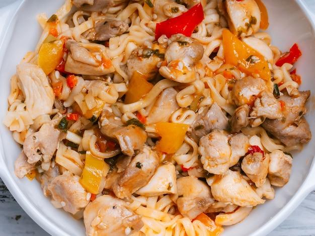 野菜と鶏肉のスパイスとホットソース入りのインスタントラーメンまたは中華鍋。伝統的なアジア料理