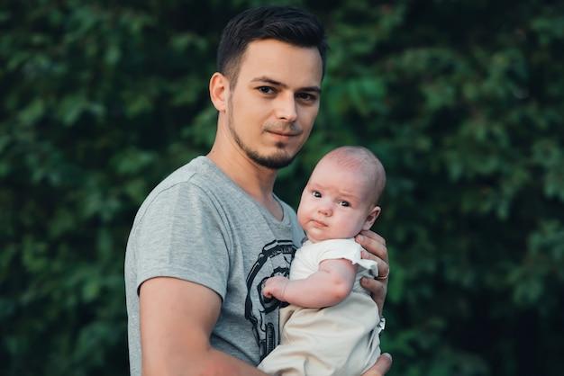 手で生まれたばかりの息子男の子と若い幸せなお父さん