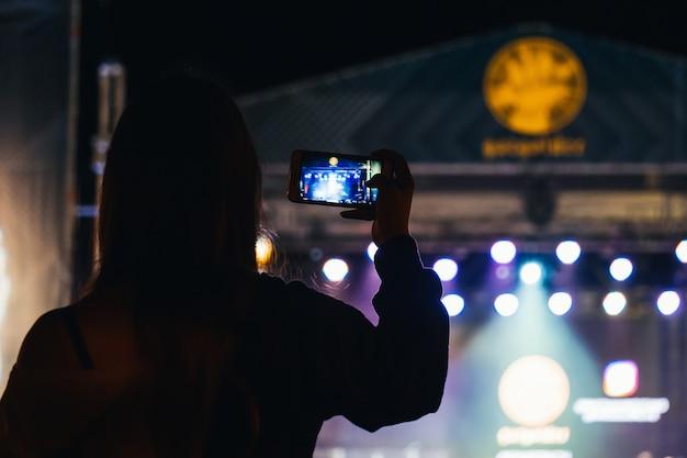 女の子はミュージシャンバスタのライブコンサートで携帯電話でビデオを撮影します。