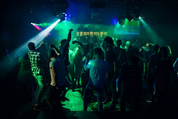 パーティーでダンスフロアにナイトクラブで踊る人々のシルエット