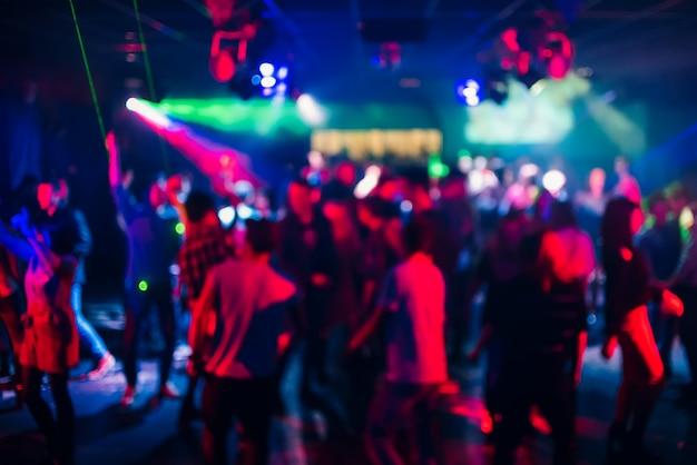 Размытые силуэты людей, танцующих в ночном клубе