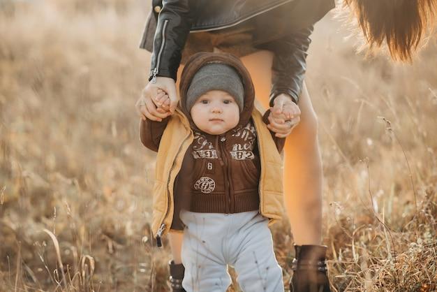 ママは彼女の男の子を散歩で手に持っています。赤ちゃんの最初のステップ