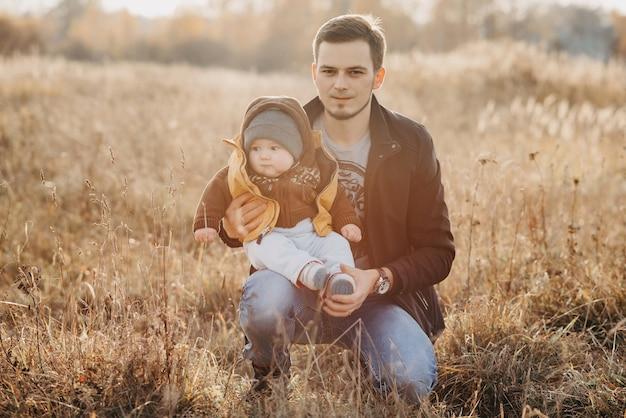 秋の自然の中で座っている息子男の子と若いお父さん