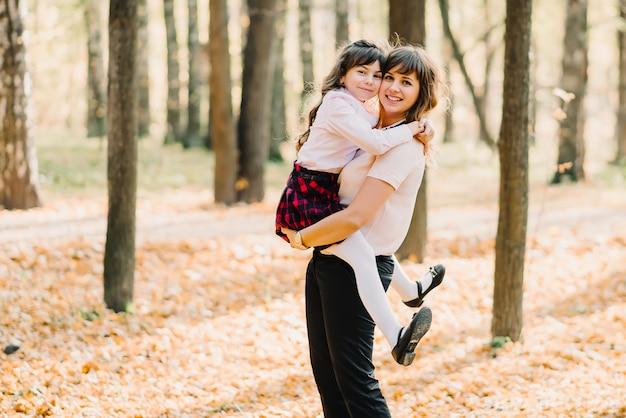 彼女の腕を笑顔で彼女の娘と一緒に幸せな母