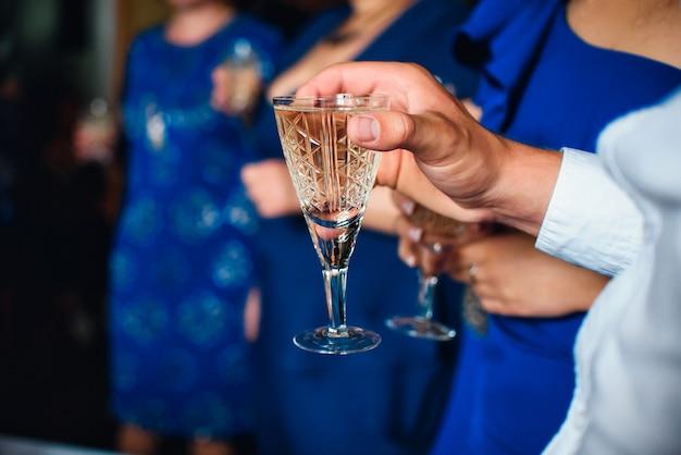 祭りで男性の手でワインのグラス