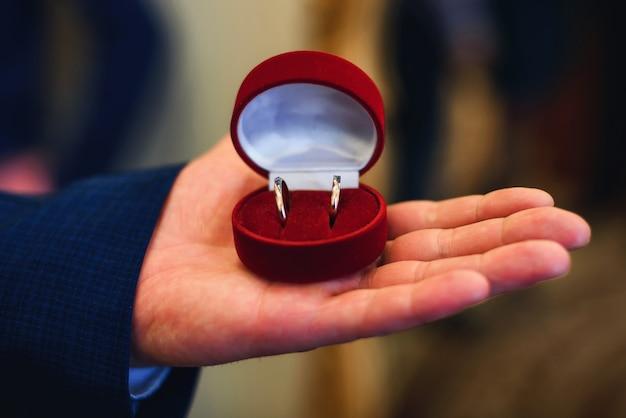 結婚のための男の手に結婚指輪の箱