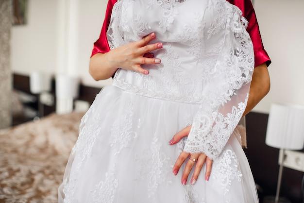花嫁は結婚式の白いドレスを保持しています