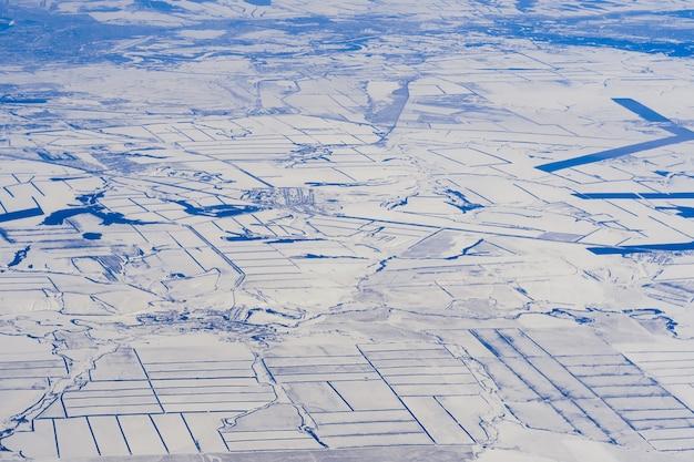 シベリアのロシアの雪の中で都市と道路の航空写真