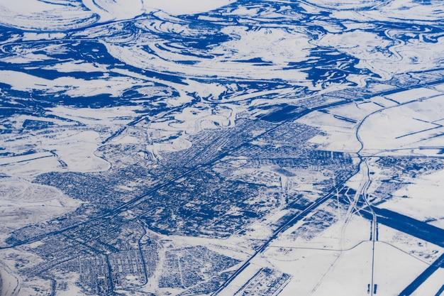 雪の中でシベリアのロシアの湖と川の飛行機からの空中写真