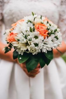 花嫁の手に白い花束を結婚式