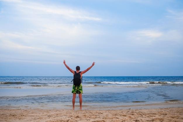 海の背景にバックパックを持つ男