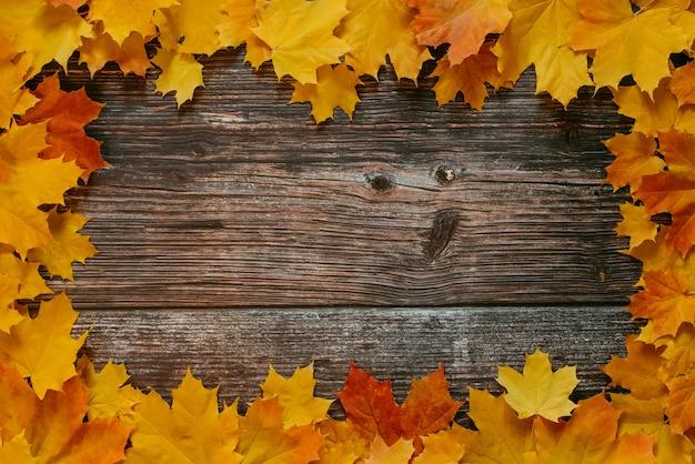 古い木製の背景にオレンジ黄色のカエデの葉の秋のフレーム