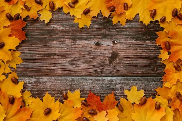 カエデの葉と木の板の背景にドングリの秋のフレーム