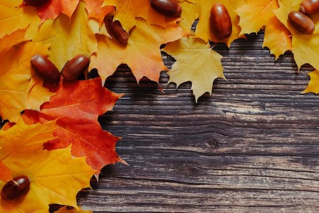 オレンジ色のカエデの葉とドングリの古い木のテクスチャのカラフルな秋の背景
