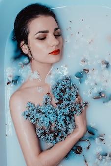 リラックスしてミルクと花とお風呂で楽しんでライラックの花束と若い裸の女の子の顔