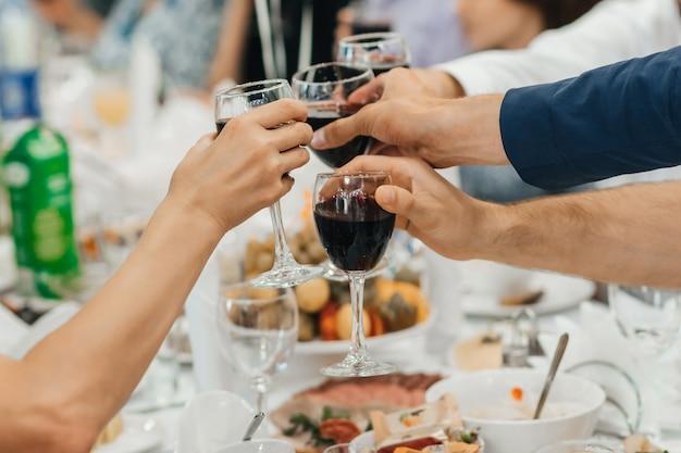 ワインのグラスをチリンと乾杯の友人のグループの手