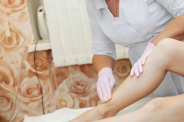 Женщина-косметолог проводит процедуру сахарной депиляции с медом на ногах лежащей девушки