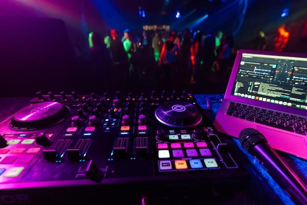 Музыкальный контроллер диджея в кабинке на фоне танцпола