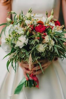 花嫁の手に赤と白のウェディングブーケ