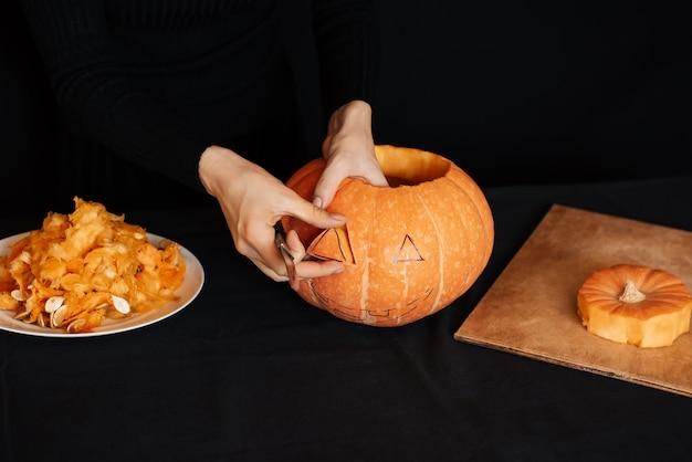 女の子の手はハロウィーンのオレンジ色のカボチャになります
