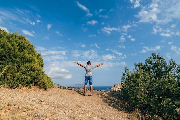 山の上に空に上げられた腕を持つ男性旅行者