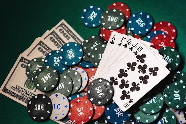 ポーカーのゲームでチップとお金の山の上のロイヤルフラッシュのカード