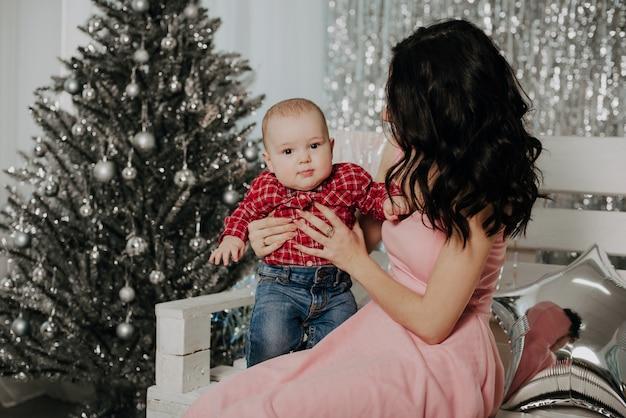 座っている生まれたばかりの少年の息子を持つ若い母親