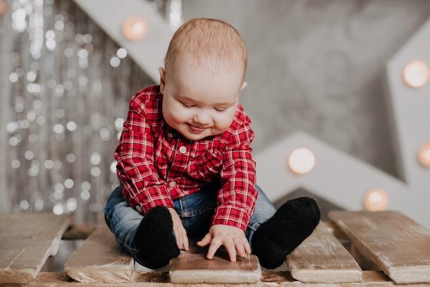クリスマスの装飾の背景の上に座って幸せな新生児少年