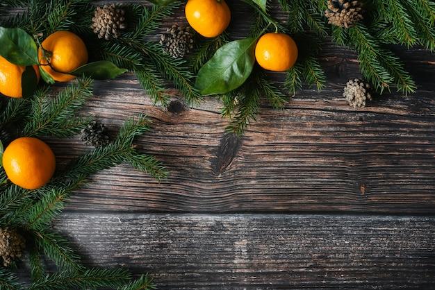 みかん、モミの枝、コーンとクリスマスの背景