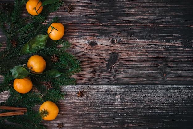 みかん、モミの枝、シナモン、スターアニスとクリスマスの背景。