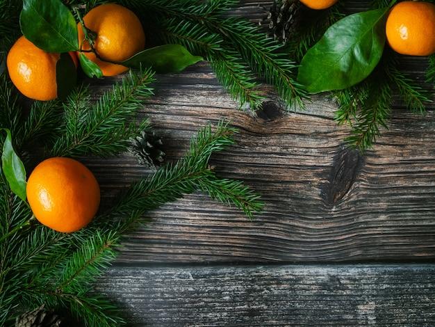 みかんとクリスマス休暇の木製の背景にモミの枝