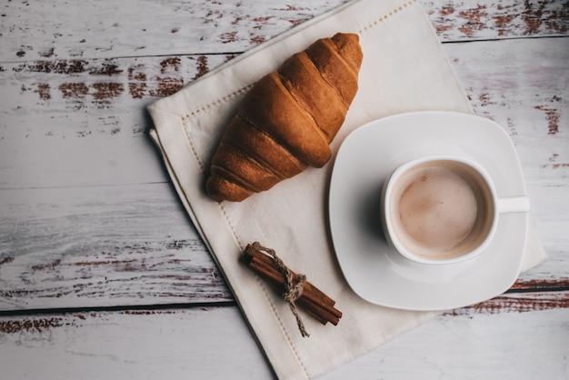 コーヒーとクロワッサンとシナモンの木製テーブルと白いカップ