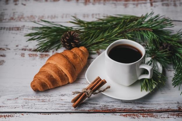 一杯のコーヒーとクロワッサンとクリスマスデコレーション
