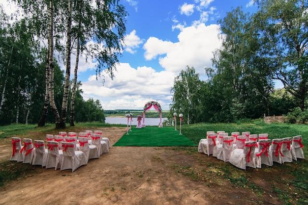 美しい結婚式のための結婚式のアーチと椅子