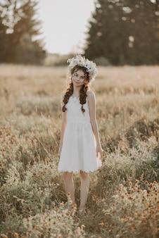 白いドレスとフィールドで夏に花の花輪の少女