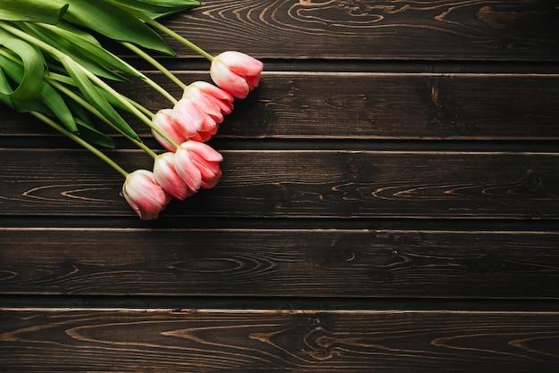 木製のテーブルにピンクのチューリップの花の花束