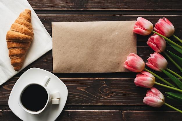 ピンクのチューリップの花とクロワッサンの花束とコーヒーのカップ