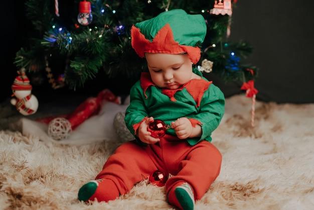 エルフの衣装の少年はボールとクリスマスツリーの下に座っています。