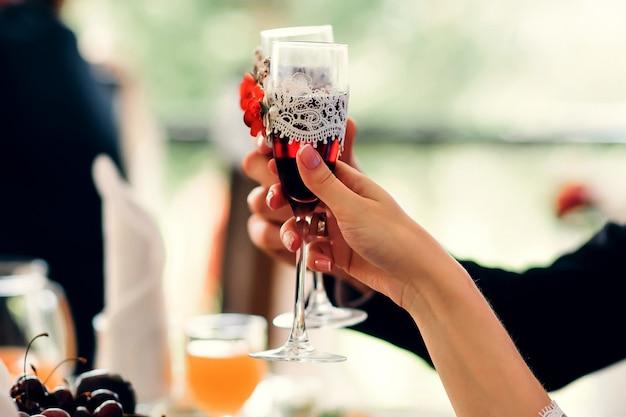 Рука жениха и невесты с красными бокалами для шампанского, украшенными на свадьбе