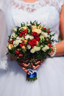 赤いバラとヒナギクの花嫁の手の中のウェディングブーケ