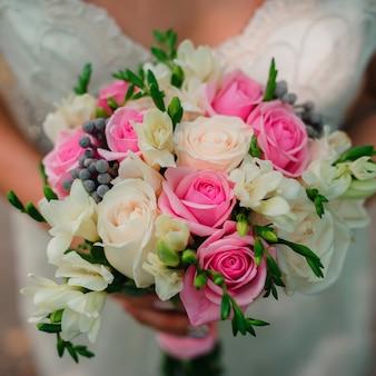 手に繊細な白とピンクのバラと美しい花束を結婚式