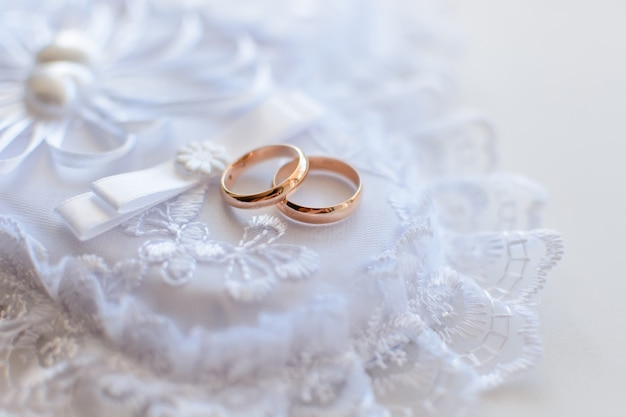 Пара золотых обручальных традиционных колец на белой кружевной подушке