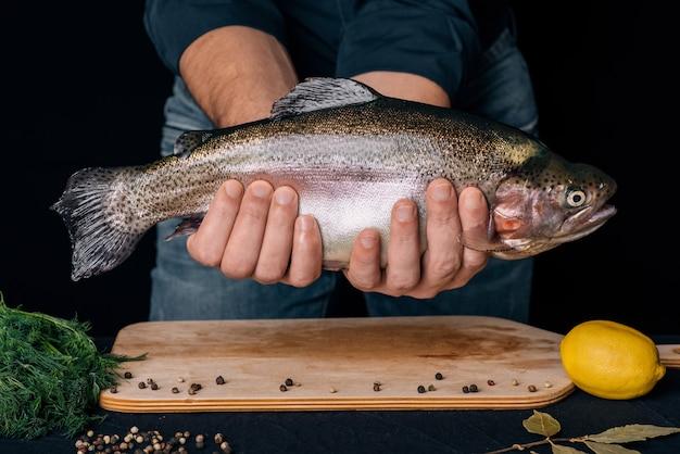 キッチンの背景に男性の手で魚します。大規模な新鮮なマス