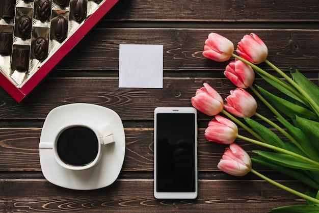 一杯のコーヒー、チョコレートの箱、スマートフォンとピンクのチューリップの花の花束