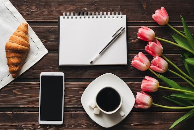 ピンクのチューリップとスマートフォンの花束で飾られたテーブルで朝食にクロワッサンとコーヒーのカップ