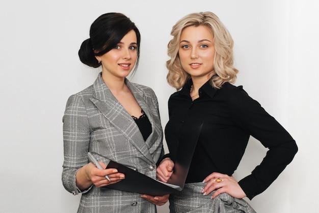 Две девушки в деловых костюмах блондинки и брюнетки-секретарши