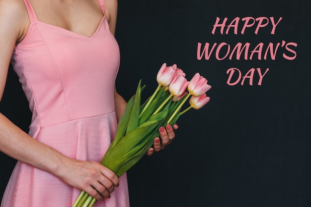 女の子の手にピンクのチューリップの花の花束。テキスト幸せな女性の日グリーティングカード