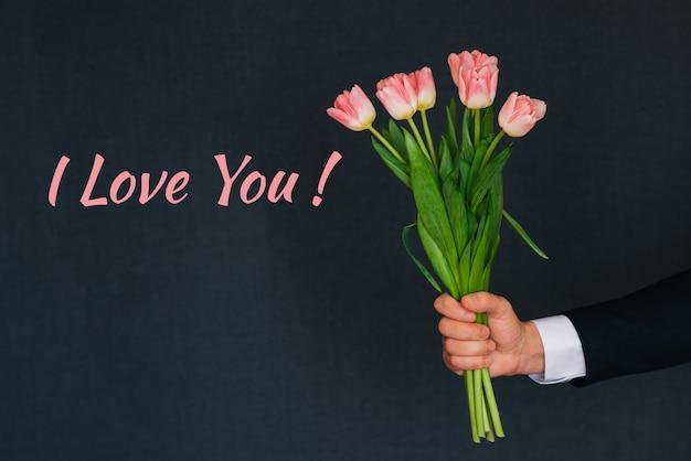 Букет из розовых тюльпанов в мужской руке. открытка с текстом я люблю тебя