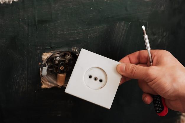 男性の電気技師は古いコンセントを削除します